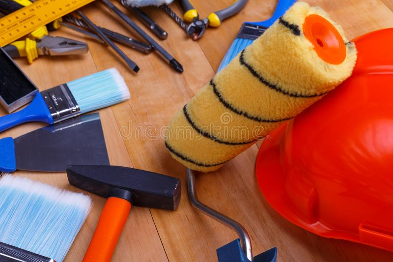Wali on a helmet with scattered tools nearby for minor repairs on a wooden background. Paint roller on the helmet with scattered screwdrivers, flat pens, hammer royalty free stock images