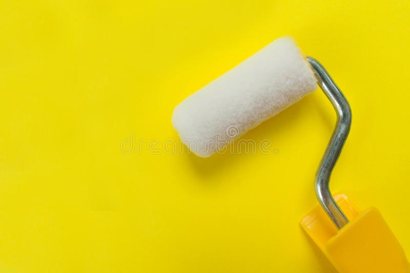Paint roller on a yellow background. Copy space royalty free stock image