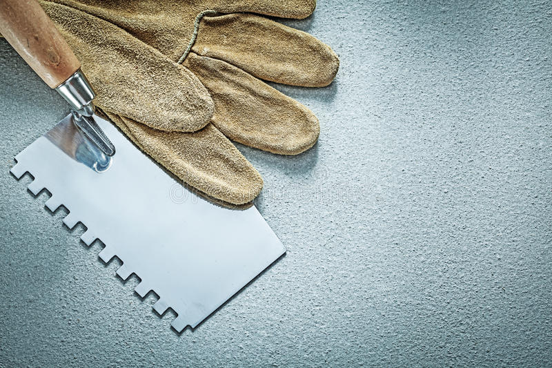 Paint scraper leather working gloves on concrete background cons. Truction concept royalty free stock photos