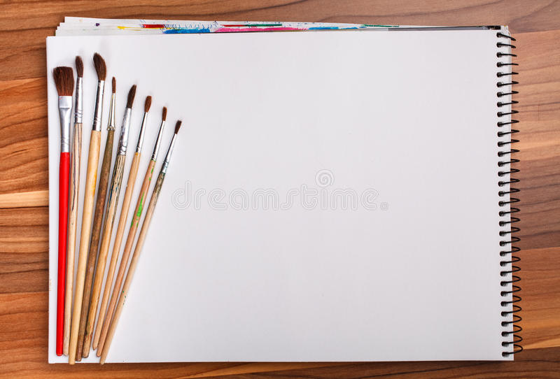 Paint and sketch book with brushes stock images
