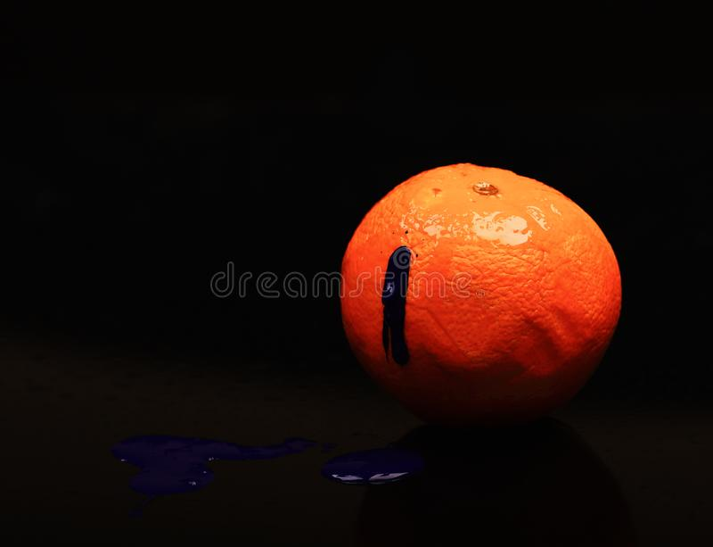 Paint splashing on orange fruit. Drops of blue oil paint. Paint splashing on orange fruit. Drops of blue oil or acrylic paint poured on fruit on black background stock photo