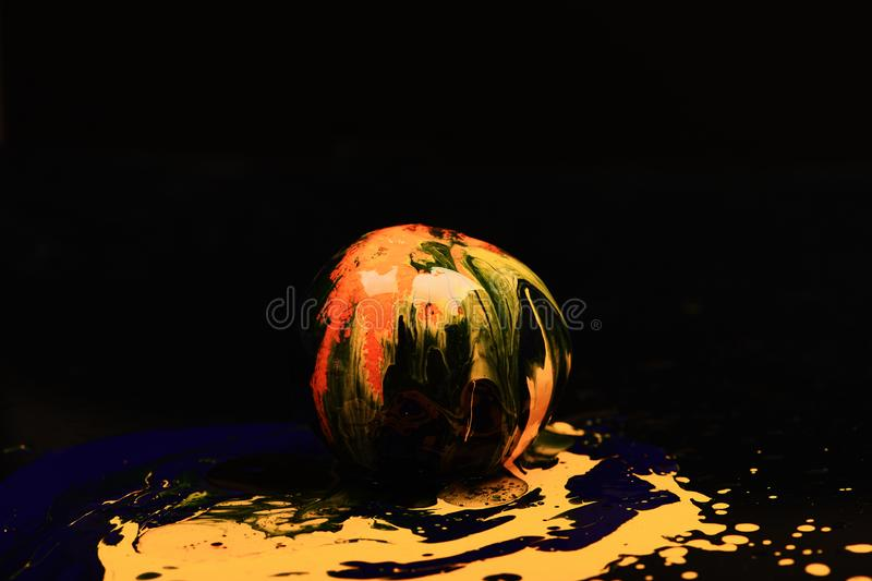 Paint splashing on orange fruit. Nutrition and food art concept. Drops of blue and yellow oil or acrylic paint poured on fruit on black background. Orange or royalty free stock photography