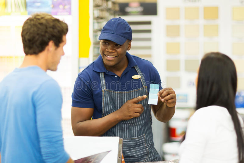 Paint store salesman helping couple royalty free stock image