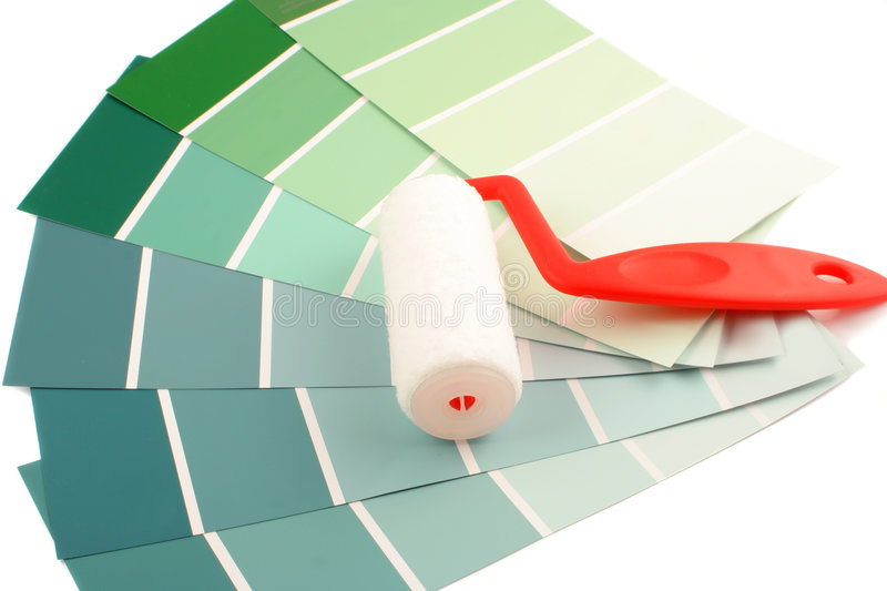Paint swatches. Green shade paint swatches, and small paint roller for home decorating royalty free stock photography