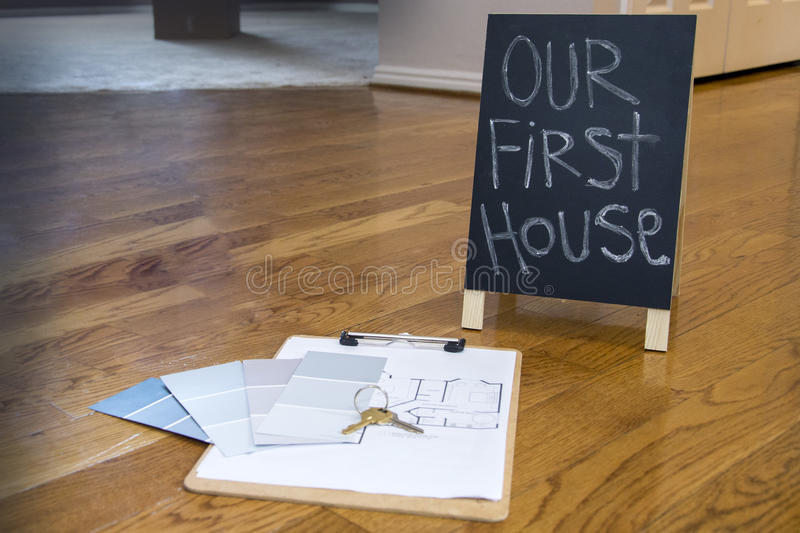 Paint swatches and house plans on floor with first house sign stock photography