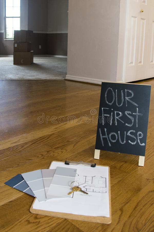 Paint swatches and house plans on floor with first house sign stock images