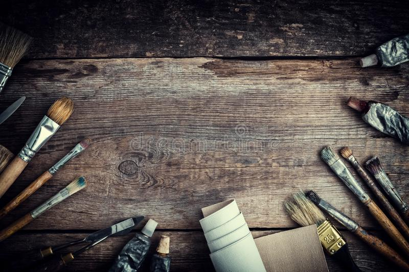 Paint tubes, brushes for painting and palette knifes on old wooden background. Top view. Flat lay. Retro toned stock image