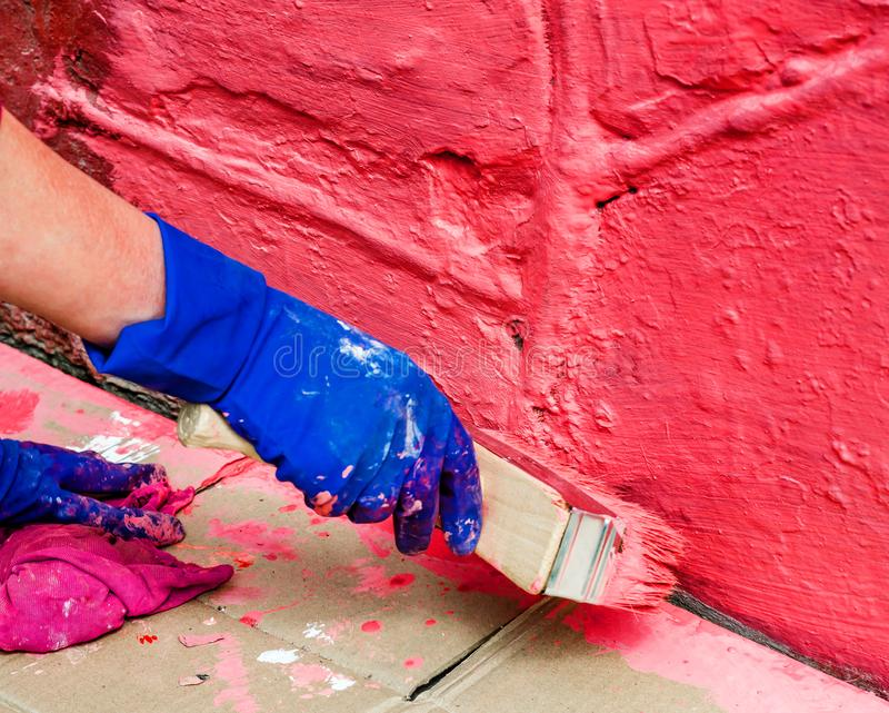Paint the wall in red with a large wide paint brush royalty free stock photos