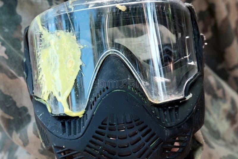 Paintball Κίτρινος λεκές στο γυαλί της προστατευτικής μάσκας σε ένα υπόβαθρο κάλυψης Η έννοια της ήττας και της απώλειας Αθλητισμ στοκ εικόνα