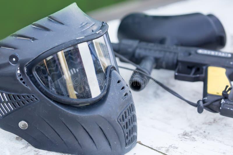Paintball ammunition. Black helmet and gun outdoors. Close up image stock photo