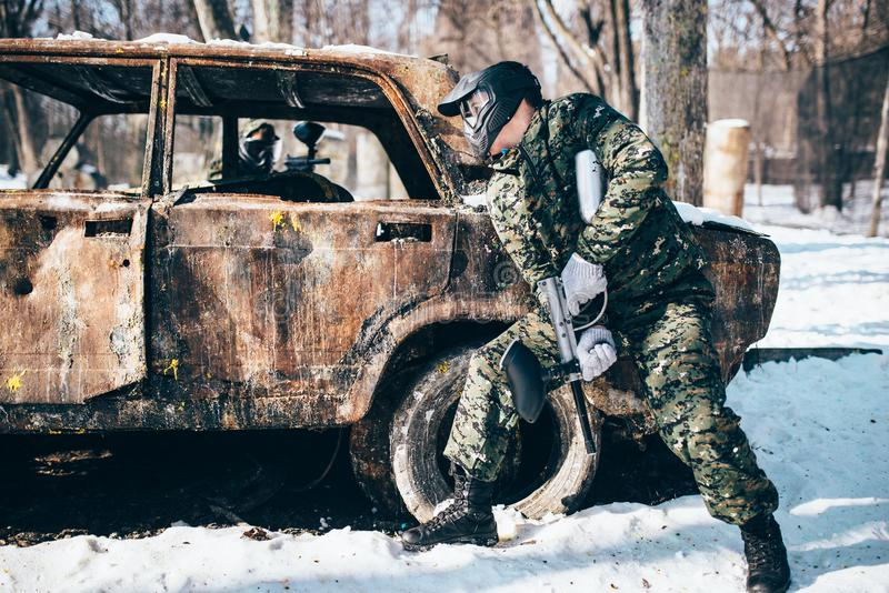 Paintball battle, burned car in winter forest. Paintball battle around burned car in winter forest, paintballing. Extreme sport, military game stock photo