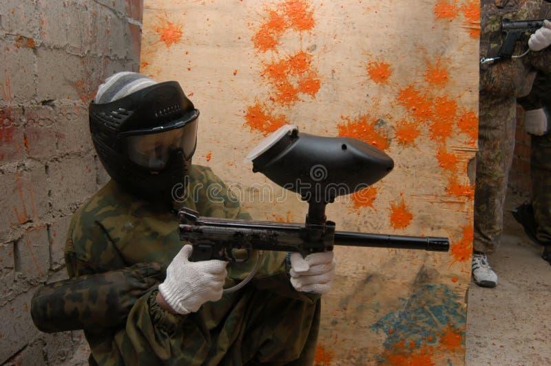 Paintball de speler verdedigt een gebouw. stock fotografie