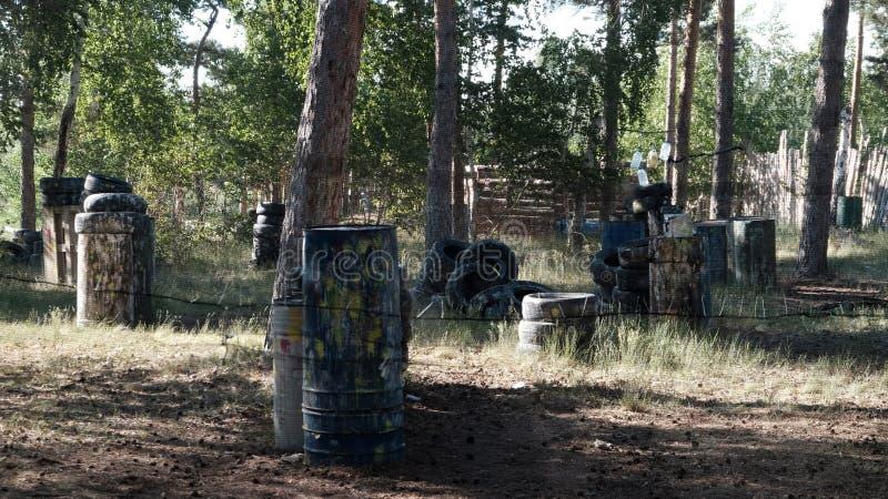 Paintball Fäktat område i skogen för leken av kriget Gamla trummor och gummihjul som skydd för spelare Bl?tthav, Sky & moln sport royaltyfri bild