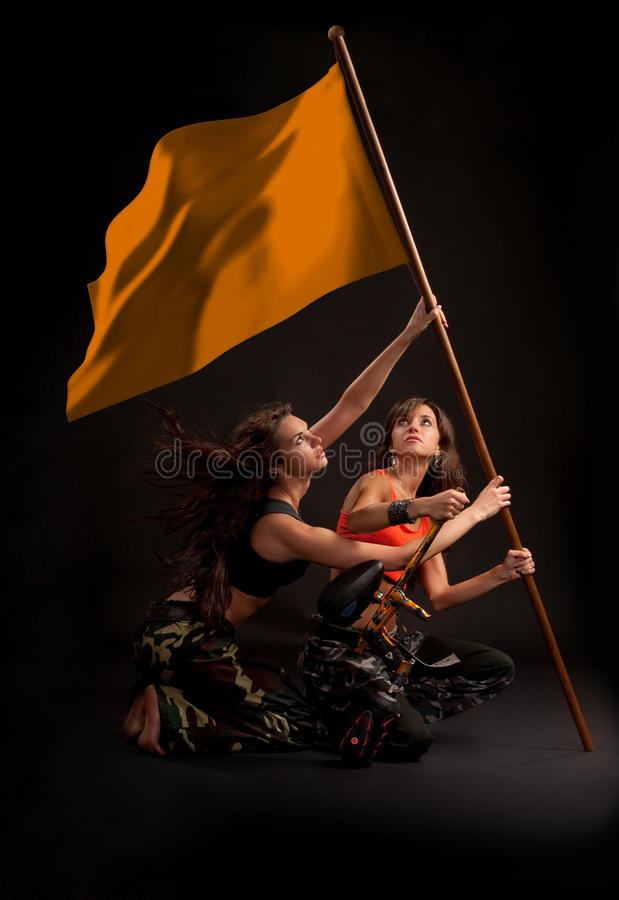 Paintball girls rising victory flag royalty free stock images