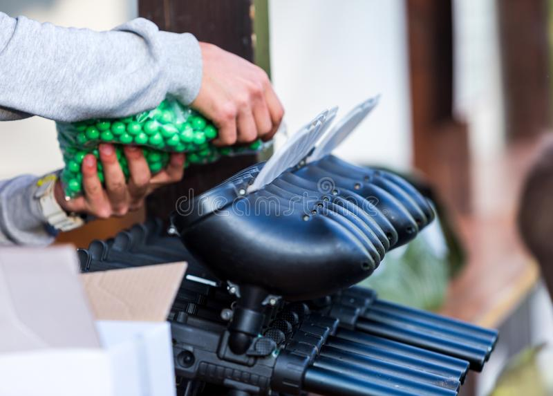 Paintball guns on the table. a man is filling gun with a balls. paintball games can be played on indoor or outdoor fields. Of varying sizes royalty free stock images