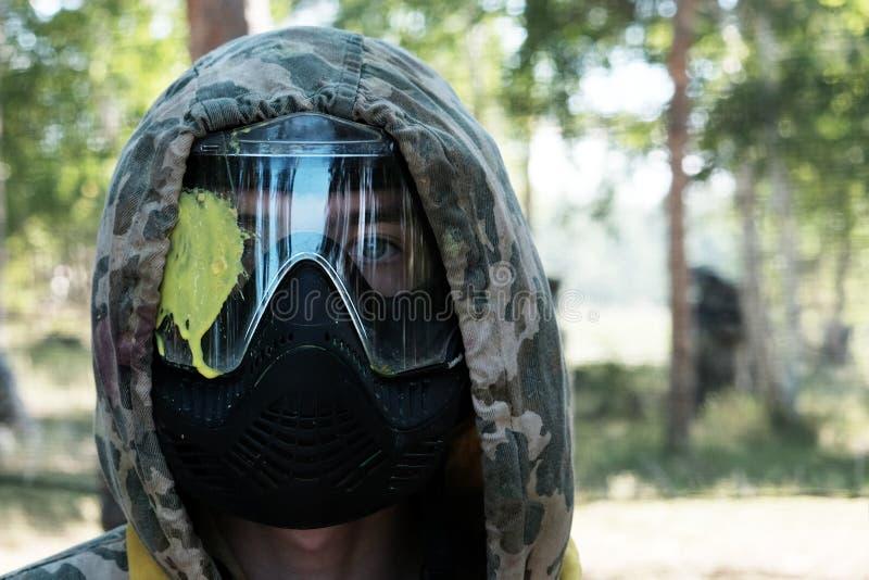 Paintball Nederlaget av spelaren i huvudet Stående av en grabb i en kamouflagehuv och en skyddande maskering med en gul fläck arkivfoto