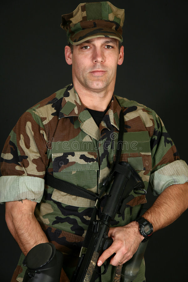 Paintball Player. Attractive thirty something man in camo fatigues with paintball rifle stock image