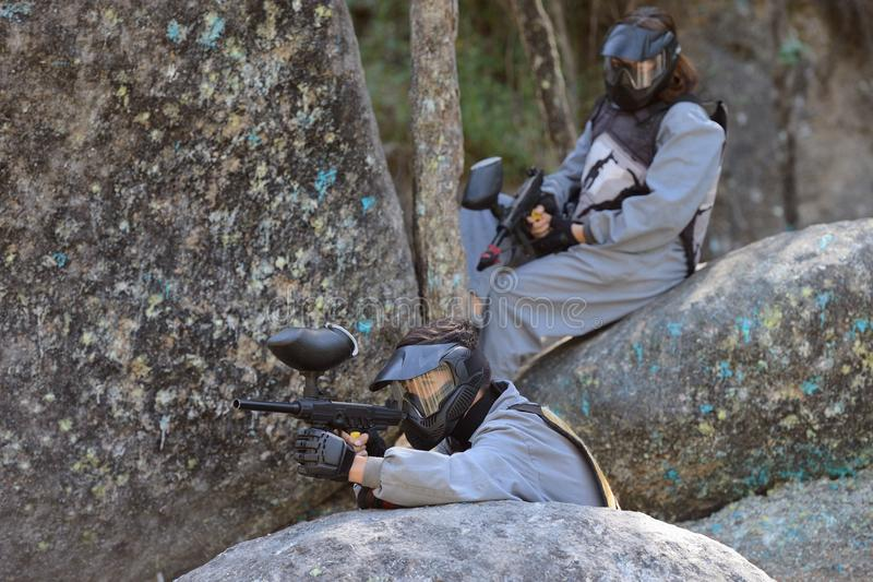 Paintball player on a boulder stock photography