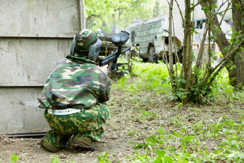 Paintball player in camouflage hides stock photo