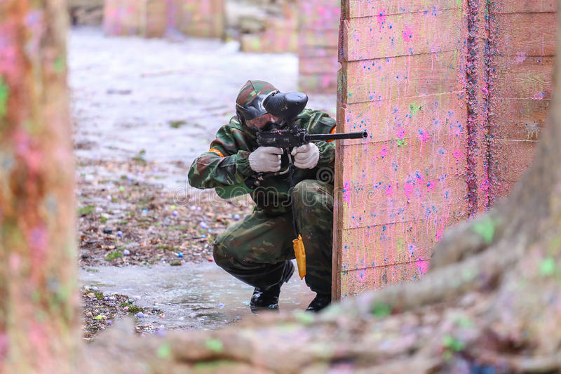 Paintball player. Man playing paintball behind the fortification stock photo