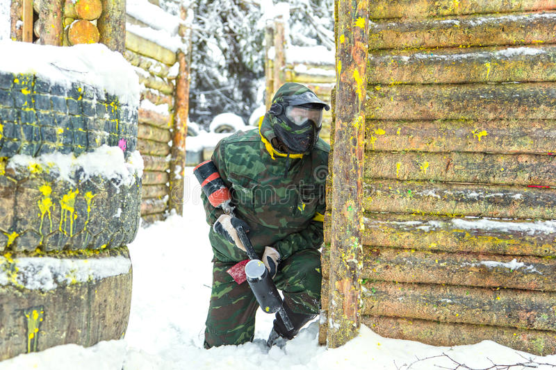Paintball player with marker sitting on snow near wooden fortification royalty free stock photo