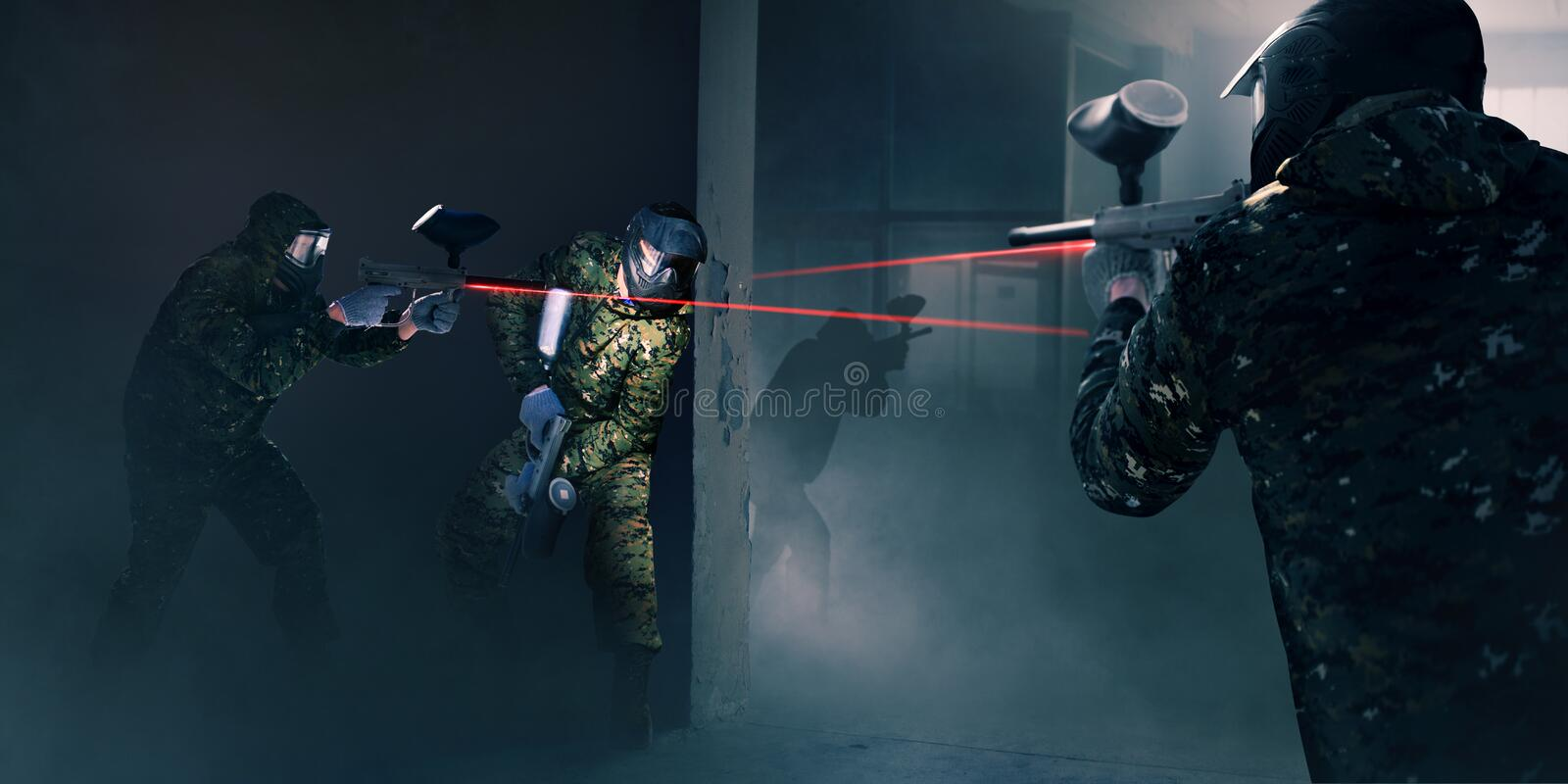 Paintball team in battle, guns with a laser sight royalty free stock photos