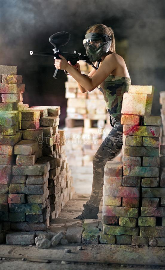 Paintballspelare med vapnet i handling arkivbilder