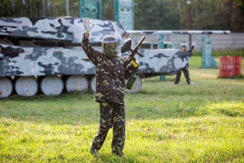 Paintballspelers in camouflage eenvormig en beschermend masker met kanon op het gebied, spruit in vijanden in de zomer Actieve sp royalty-vrije stock foto