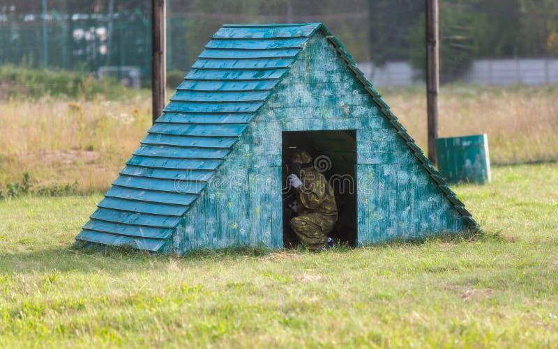 Paintballspelers in camouflage eenvormig en beschermend masker met kanon op het gebied, spruit in vijanden in de zomer Actieve sp royalty-vrije stock fotografie