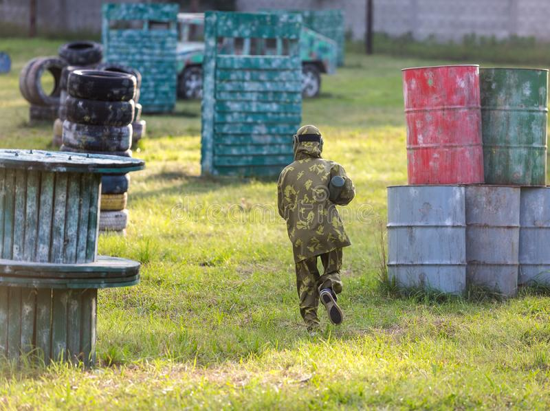 Paintballspelers in camouflage eenvormig en beschermend masker met kanon op het gebied, spruit in vijanden in de zomer Actieve sp stock foto