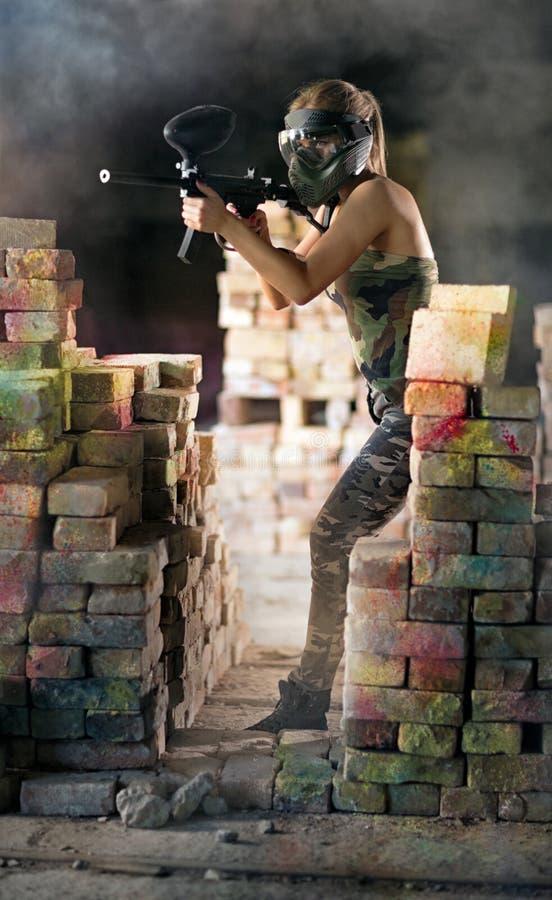 Paintballspieler mit Gewehr in der Aktion stockbilder