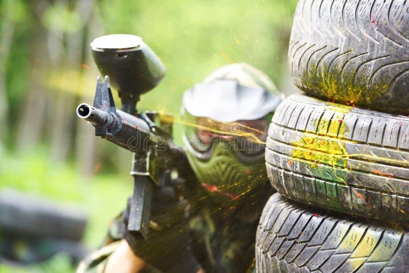 Paintballspieler unter Kanonenschuß lizenzfreies stockfoto