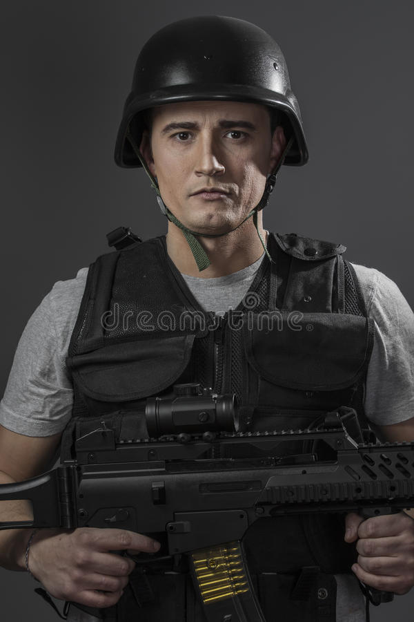 Paintballsportspelare som bär den skyddande hjälmen som siktar pistolen, arkivbild