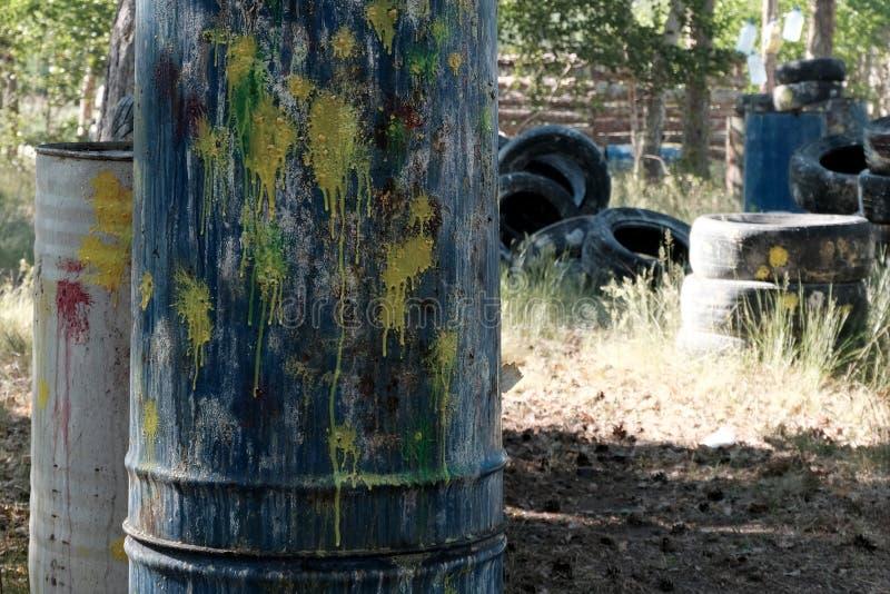 Paintballterritorium Närbild av trummor av färgfläckar från paintballvapenskott Gamla gummihjul från bilen som ett skydd Bakgrund royaltyfria foton