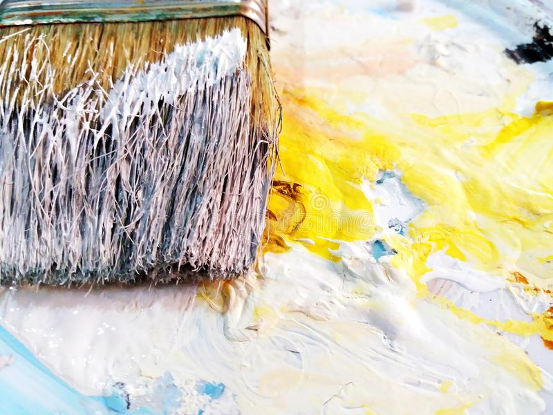 Paintbrush be stained water color with white, blue and yellow color on palette and right copy space. stock photo