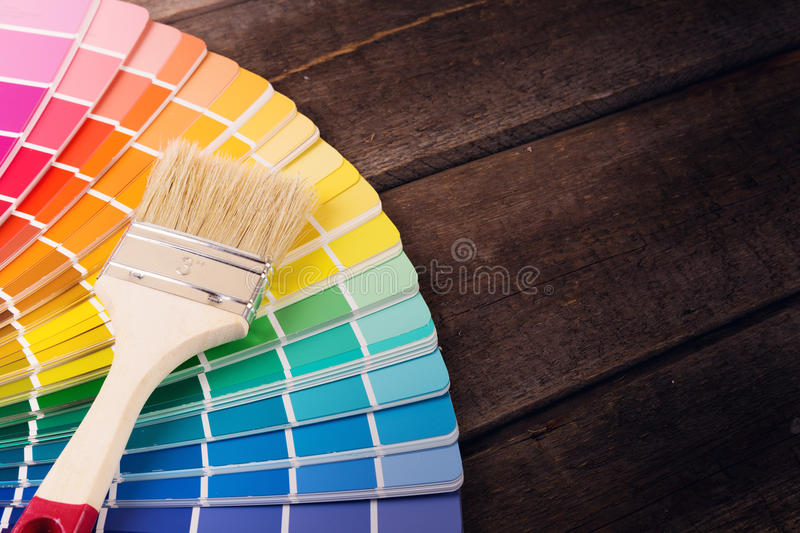 Paintbrush on colorful paint swatches. With copy space stock images
