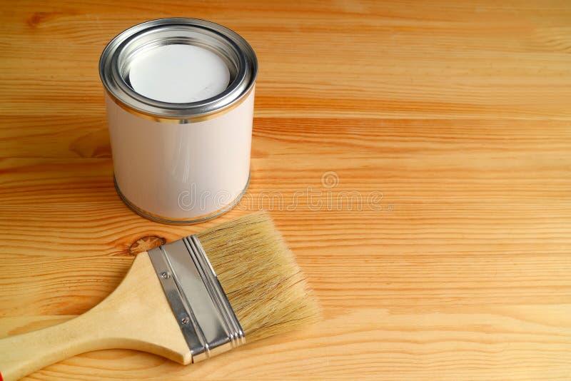 Paintbrush i farba możemy odosobniony na drewnianym tle z bezpłatną przestrzenią fotografia stock