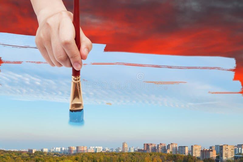 Paintbrush maluje dayly niebieskie niebo od czerwonego wschodu słońca fotografia stock