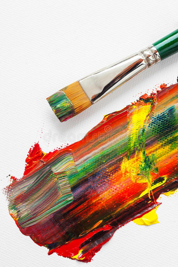 Paintbrush and mixed rainbow oil paints on artist canvas. Paintbrush and mixed rainbow oil paints on white artist canvas royalty free stock photos