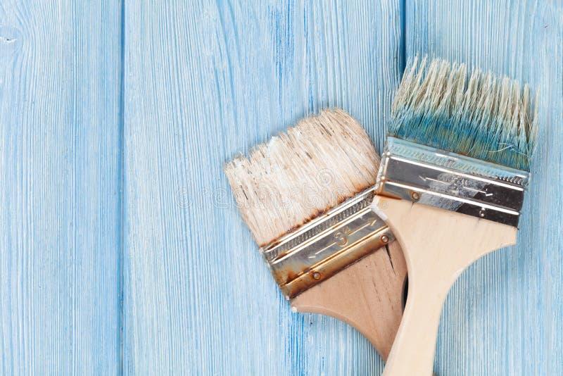 Paintbrush nad błękitnym drewnem zdjęcia stock