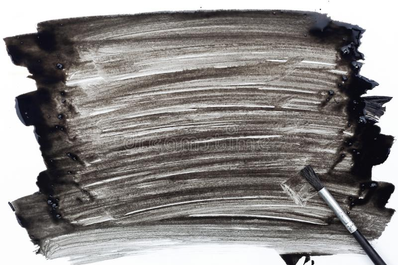 Paintbrush and paint black color on white paper. royalty free stock photography