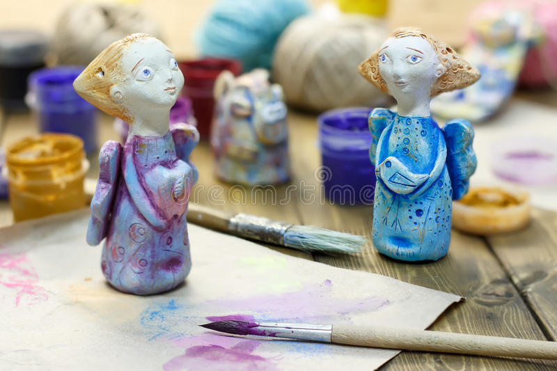 Paintbrush, paint in jars and handmade figurines `Angels of tender emotion` from clay pottery on wooden table. stock image