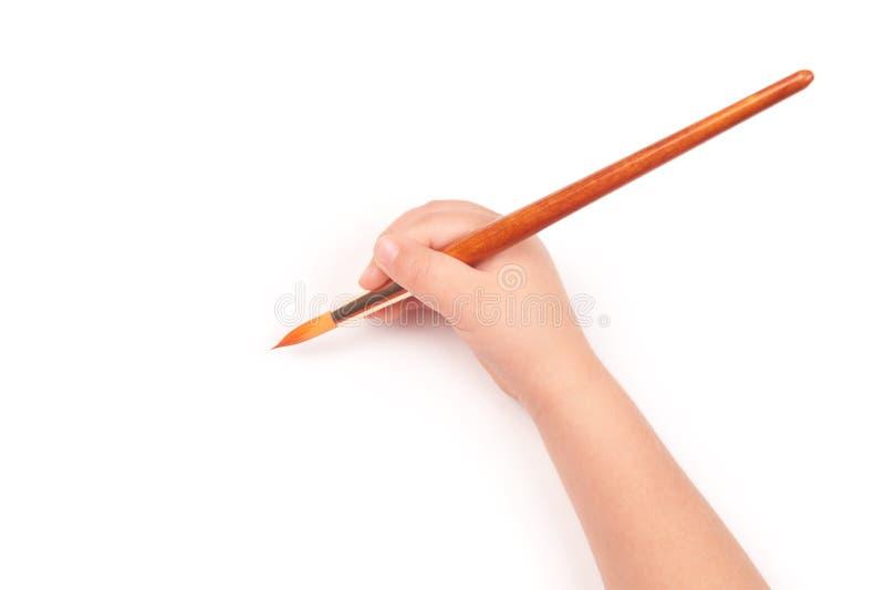 Paintbrush w dziecko ręce fotografia stock