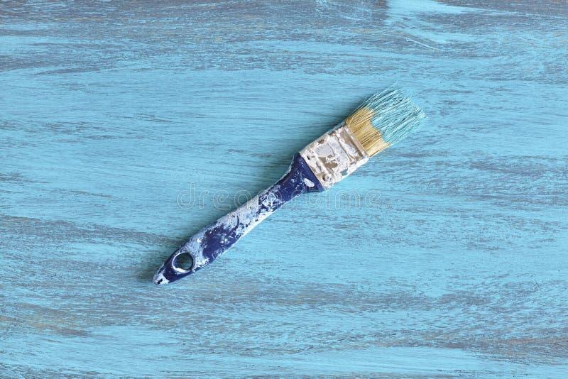 Paintbrush z błękitną farbą na drewnianej desce obraz royalty free