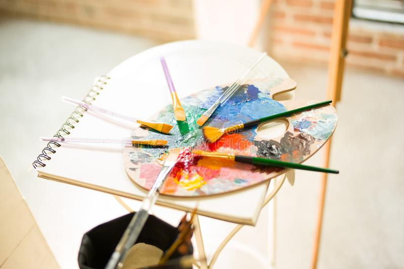 Paintbrushes on artist canvas covered with oil paint with palette closeup stock images