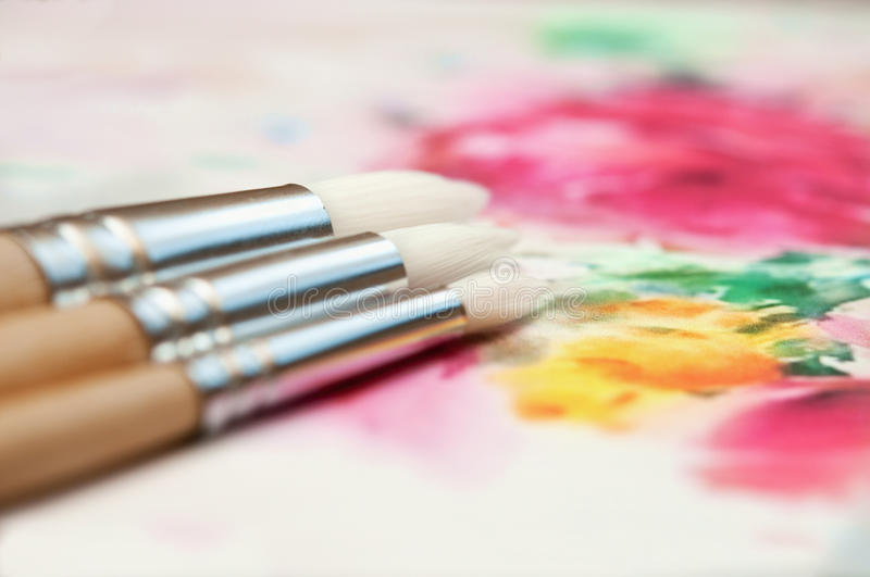 Paintbrushes over the paint background. stock image