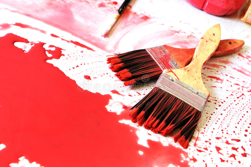 Paintbrushes and the red colour. A detailed view of composition with some paintbrushes and the red colour, over a white surface, landscape cut stock photography