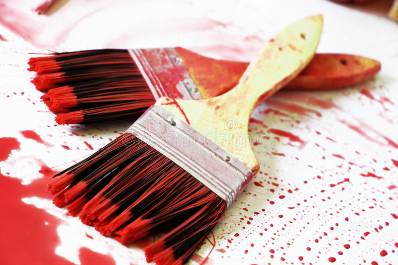Paintbrushes and the red colour. A detailed view of composition with two paintbrushes and the red colour, over a white surface, landscape cut royalty free stock photography