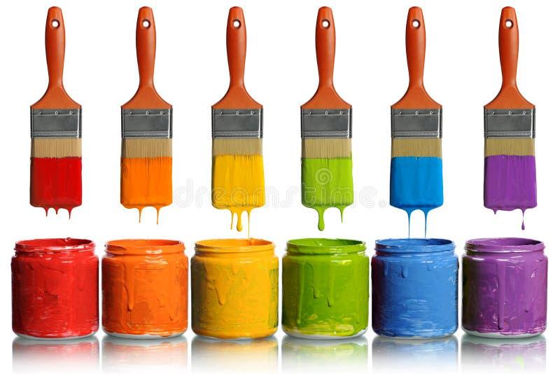 Paintbrushes som är genomblöta in i målarfärgbehållare royaltyfri foto