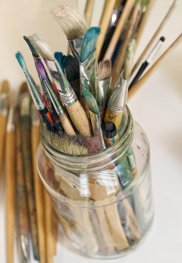 Paintbrushes. Stack of old paintbrushes standing in a jar in an art classroom royalty free stock images